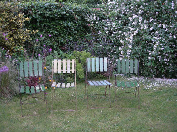 Green vertical slat garden chairs in a line